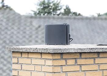 Draftbooster i sort monteret på murstensskorsten